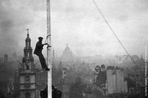 A steeplejack painting the flagstaff on Australia House, London, with St Clements Dane Church behind him. (Photo by J. A. Hampton/Topical Press Agency/Getty Images). 18th April 1934